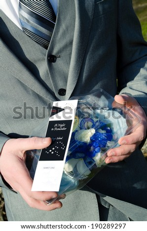Young man ready for prom wearing suit and holding a ticket and corsage. - stock photo