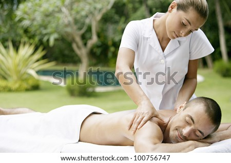 Young man receiving a massage in a tropical garden near a swimming pool. - stock photo