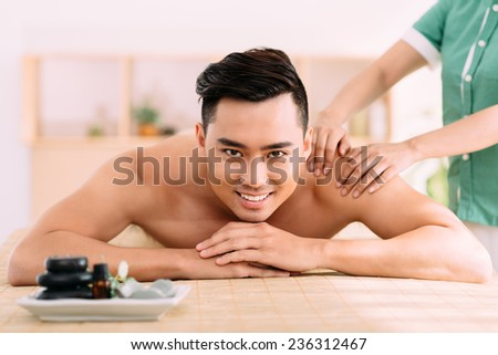 Young man receiving professional back massage at the beauty salon - stock photo