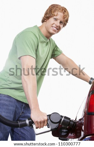 Young man refueling a car - stock photo