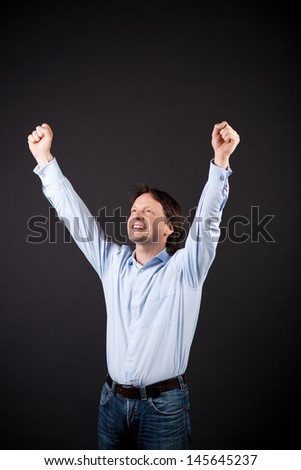 Young man rejoicing raising his fists to the air in jubilation at a personal victory or success on a dark background - stock photo