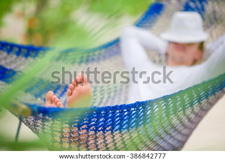 Young man relax in hammock at exotic tropical vacation - stock photo