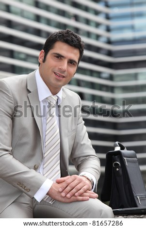 Young man relaxed sitting on a bench - stock photo