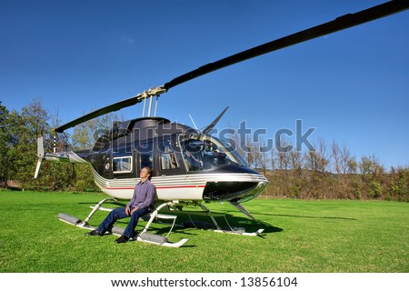 Young man relaxes next to small private helicopter on grass in estate. Shot  near Cape Town, Western Cape, South Africa. - stock photo