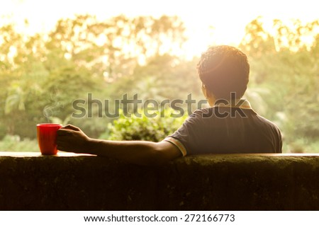 Young man relaxing in a garden having hot coffee in afternoon - stock photo