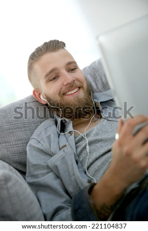 Young man relaxing in sofa, listening to music - stock photo