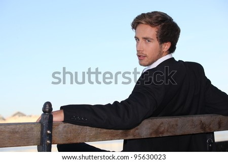 Young man relaxing on a bench - stock photo
