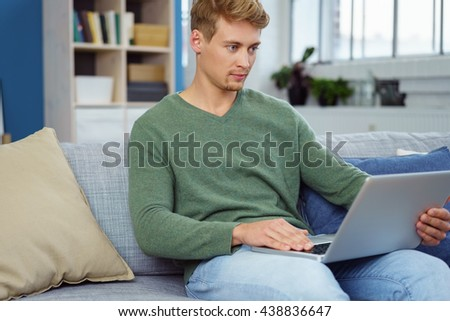 Young man relaxing on a sofa with his laptop reading the screen with a serious expression as he surfs the internet - stock photo