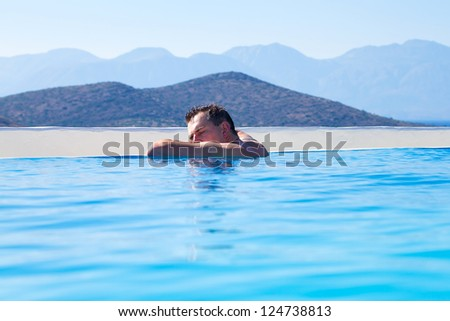 Young Man relaxing on edge of swimming pool  in Greece - stock photo