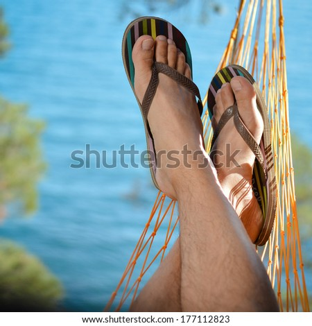 Young man relaxing on hammock at beach on summer sea outdoors background  - stock photo