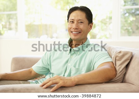Young Man Relaxing On Sofa At Home - stock photo
