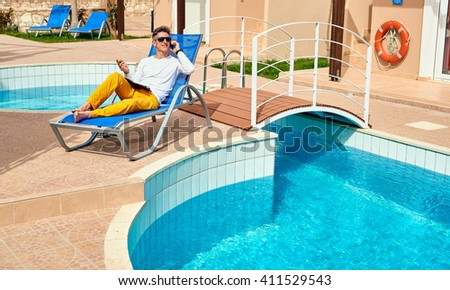 young man relaxing on the chaise-longue near the pool. man talks by phone - stock photo