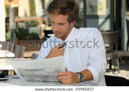 Young man relaxing reading newspaper - stock photo