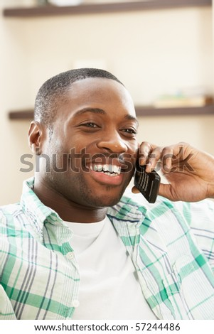Young Man Relaxing Sitting On Sofa At Home Talking On Phone - stock photo
