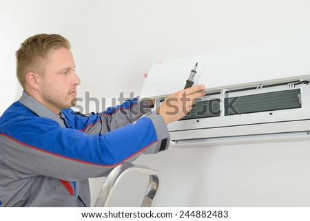 Young Man Repairing Air Conditioner Standing On Stepladder - stock photo