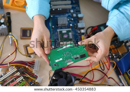 Young man repairing computer hardware in service center - stock photo