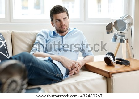 Young man resting at home on sofa. - stock photo