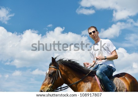 young man ride horse farm animal with blue sky in background - stock photo