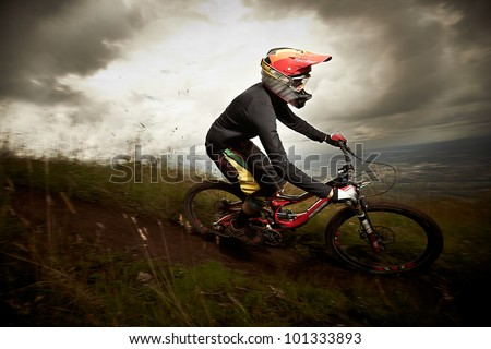 Young man riding a mountain bike downhill style - stock photo