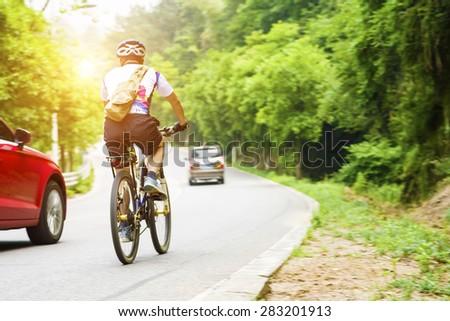 young man riding a mountain bike on mountain trail - stock photo