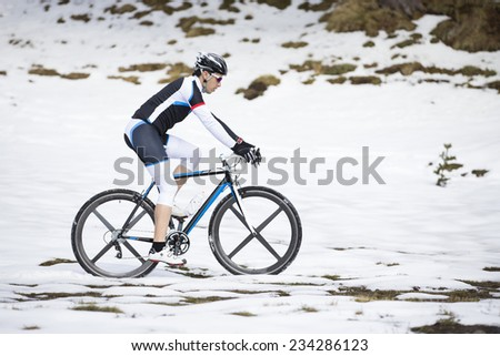 Young man riding a mountain bike on snow - stock photo