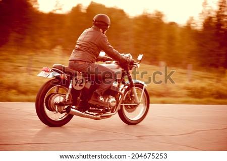 Young man riding a vintage motorcycle converted to a cafe racer. Fake license plate number. Short depth of field. Camera panning for motion blur. - stock photo