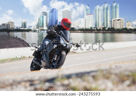young man riding big bike motorcycle on city road against urban and town building scene background use for people and convenience vehicle to traveling in town - stock photo