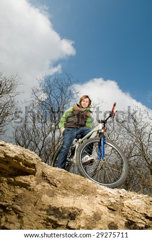 Young man riding bike, low angle view - stock photo