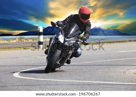 young man riding motorcycle in asphalt road curve with rural and mountain background - stock photo