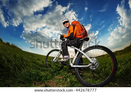 Young man riding on bicycle through deep grass with red backpack against blue sky - stock photo