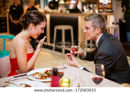 Young man romantically proposing to girlfriend and offering engagement ring - stock photo