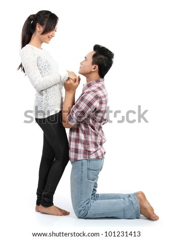 Young man romantically proposing to girlfriend isolated on white background - stock photo