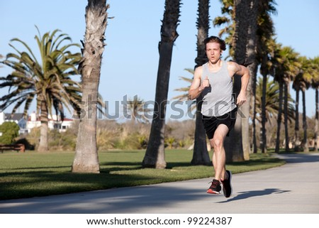Young man running by the beach - stock photo