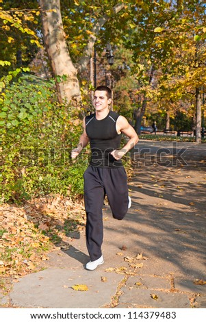 Young man running in a beautiful autumn park - stock photo