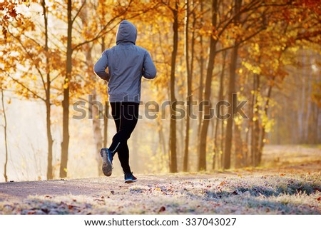 Young man running in the park during autumn morning - stock photo