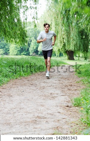 Young man running in the park in the morning - stock photo