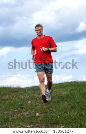 Young man running on a green field  - stock photo