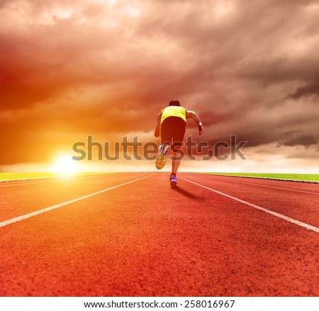 young man running on the track with sunrise background - stock photo
