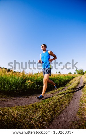 Young man running outdoors - stock photo