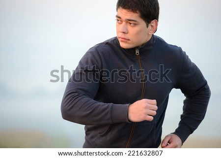 Young man running outdoors in the morning. - stock photo