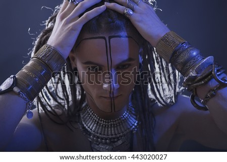 Young man's portrait. Stylish handsome sexy Guy with Dreadlocks and ethnic Jewelry, Accessories (necklace, bracelet) Close-up face. Tribal Style. Trendy youthful man's look, war paint - stock photo