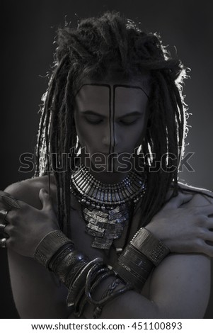 Young man's portrait. Stylish handsome sexy Guy with Dreadlocks and ethnic Jewelry, Accessories (necklace, bracelet) Close-up face. Tribal Style. Trendy egypt youthful man's look, war paint - stock photo