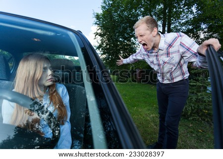 Young man screaming at a woman in car - stock photo