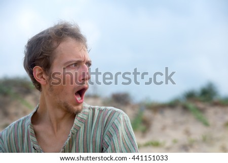 Young man screaming expressing emotions - stock photo