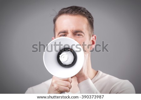 Young man screaming with a megaphone on grey background - stock photo