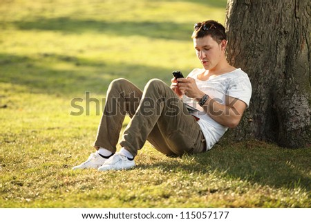 young man sending text to his girlfriend - stock photo