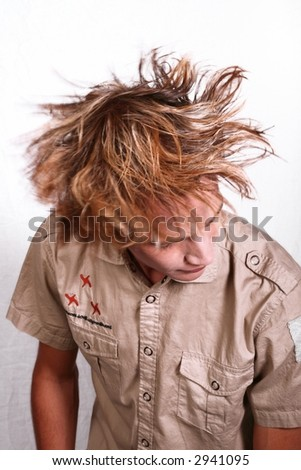 Young man shaking his head with hair in motion - stock photo