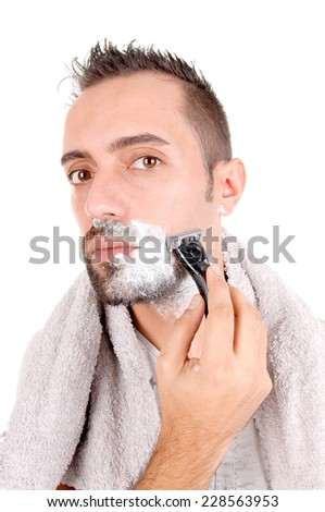 young man shaving his face isolated in white background - stock photo