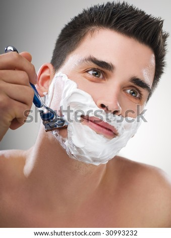 Young Man shaving with razor close up - stock photo