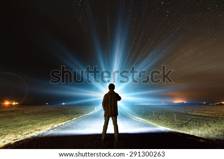 Young man shining a powerful torch on a starry night in Iceland, looking for the northern lights or aliens - stock photo